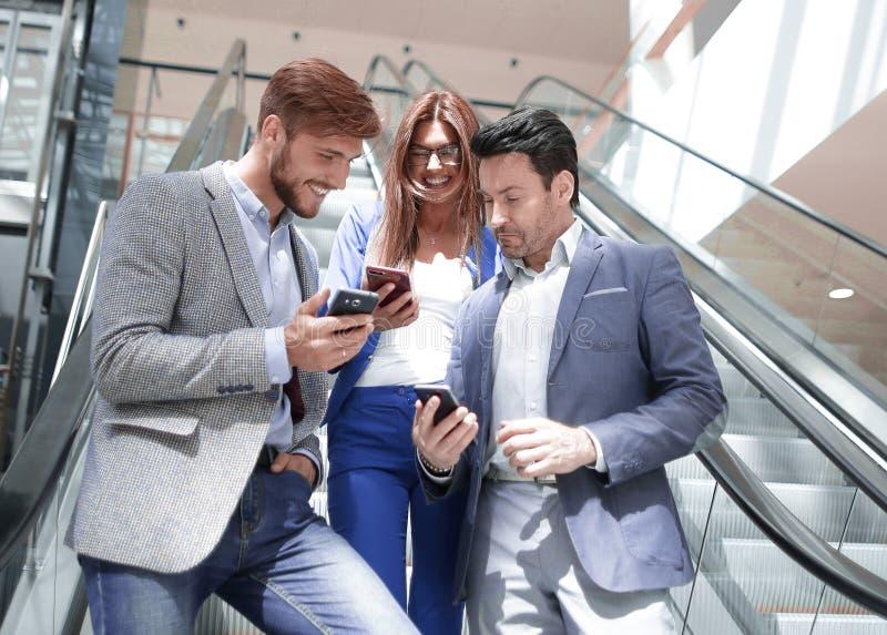 Gruppo di giovani uomini d'affari che esaminano gli schermi dei loro smartphones fotografie stock libere da diritti