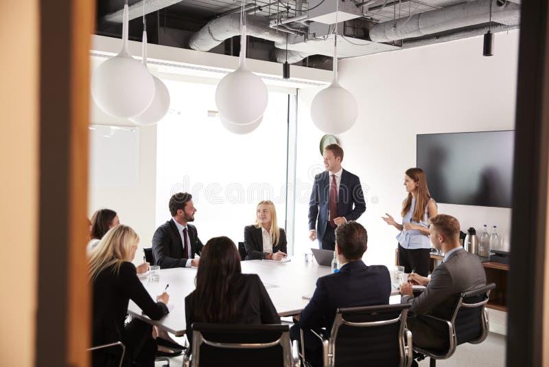 Gruppo di giovani uomini d'affari e di donne di affari che si incontrano intorno alla Tabella al giorno laureato di valutazione d fotografia stock libera da diritti