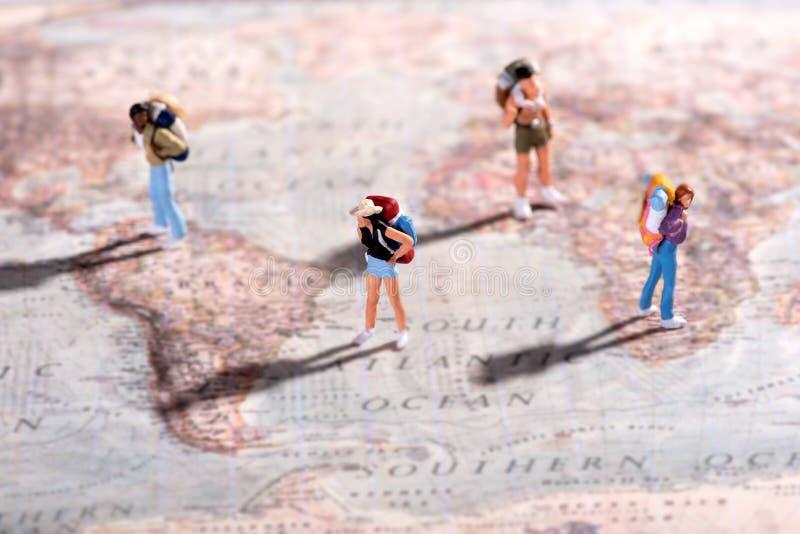 Gruppo di giovani viaggiatori su una mappa di mondo fotografia stock libera da diritti