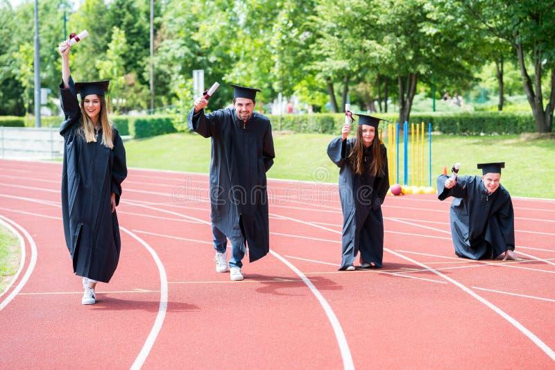 Gruppo di graduazione di studenti che celebrano sulla pista atletica, preparazione fotografia stock libera da diritti