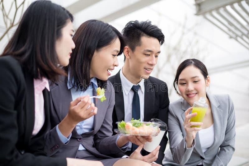 Gruppo di gruppo di affari che mangia insalata fuori dell'ufficio fotografie stock