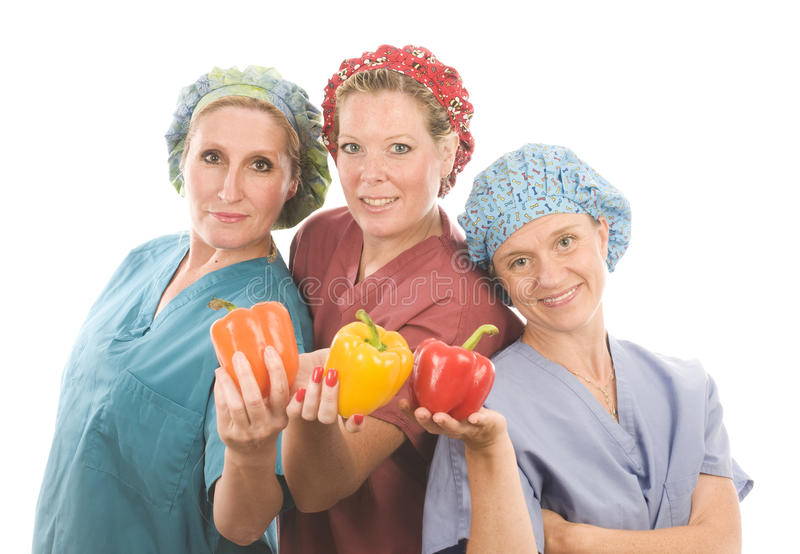 Gruppo di infermiere con le frutta e le verdure sane immagini stock
