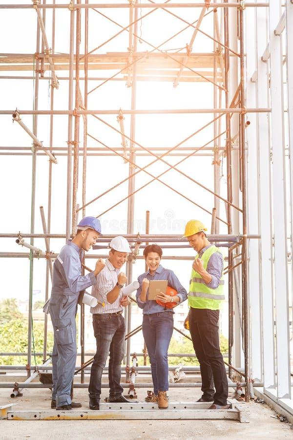 Gruppo di ingegneri, uomo e donna, lavorando insieme nel cantiere, stante sul ponte fra l'impalcatura, luce arancio del sole immagine stock libera da diritti