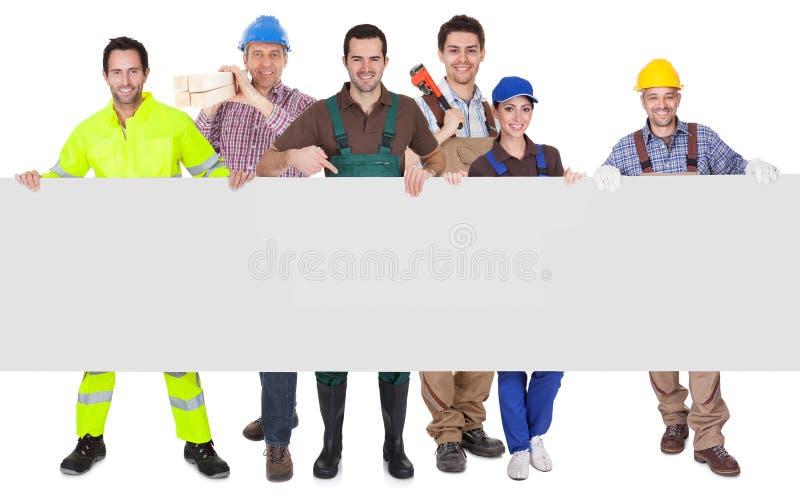 Gruppo di lavoratori che presentano insegna vuota fotografia stock