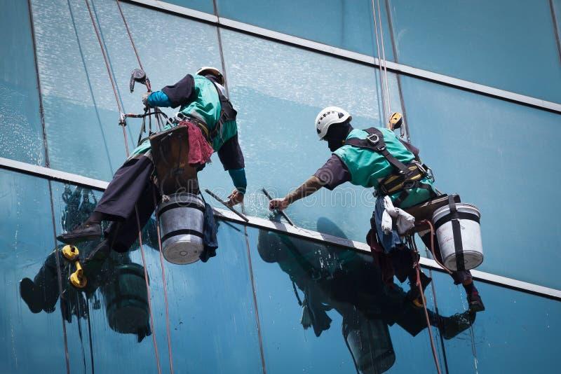 Gruppo di lavoratori che puliscono servizio di Windows su grattacielo fotografia stock libera da diritti
