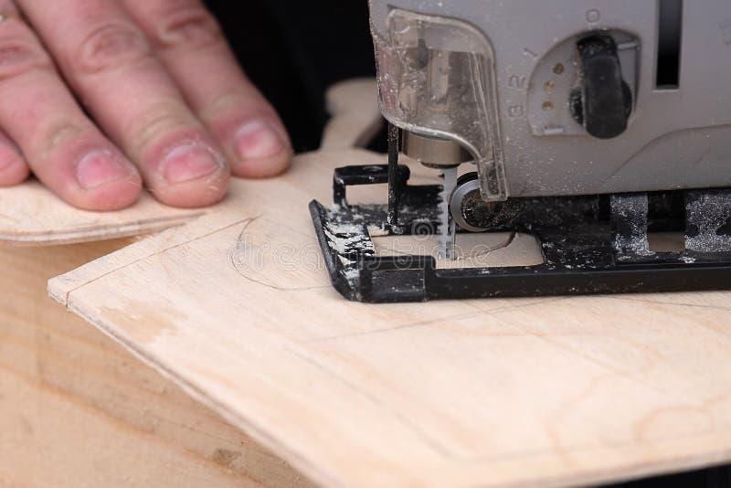 Gruppo di lavoro del lavoro in metallo di lavoro sul taglio delle forme difficili di legno un puzzle elettrico fotografia stock