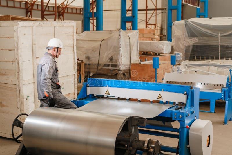 Gruppo di lavoro di fabbricazione I lavoratori regola la macchina nel magazzino la produzione di ventilazione e delle grondaie St fotografia stock
