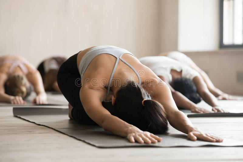 Gruppo di lezione di pratica di yoga della gente sportiva, facente il exerc del bambino immagine stock libera da diritti