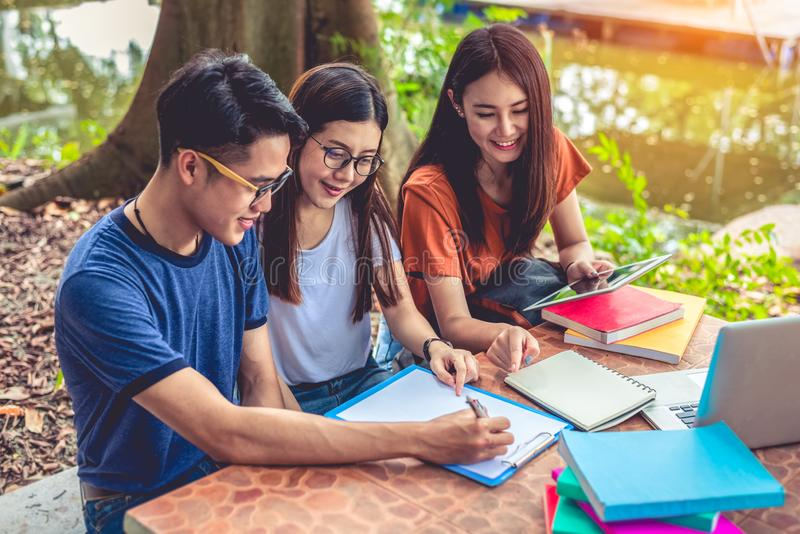 Gruppo di libri di lettura asiatici dello studente di college e classe speciale di ripetizioni per esame sulla tavola a all'apert fotografia stock libera da diritti