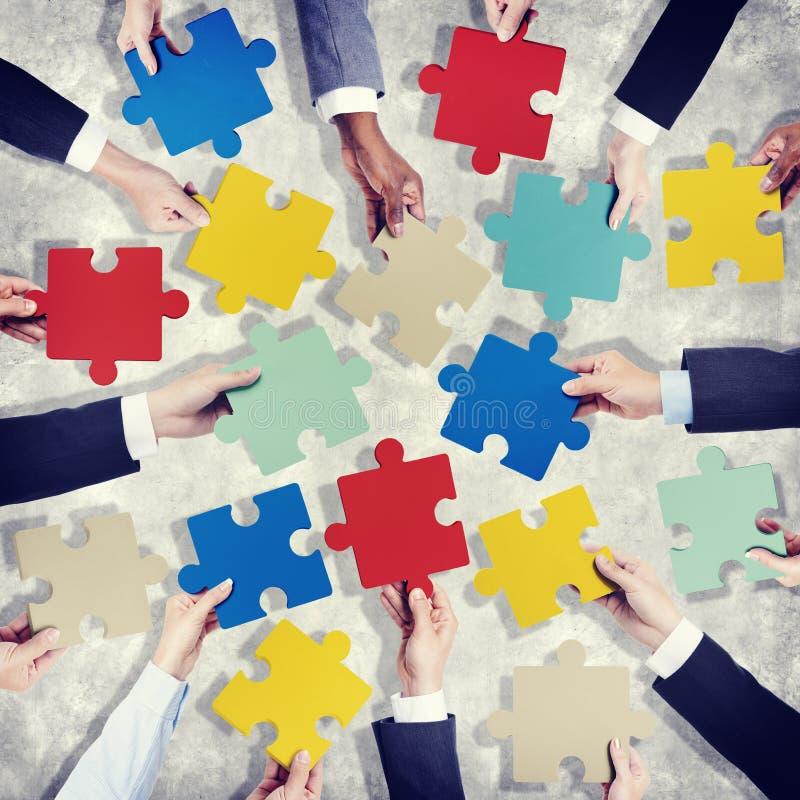 Gruppo di mani che tengono i pezzi Colourful del puzzle fotografie stock