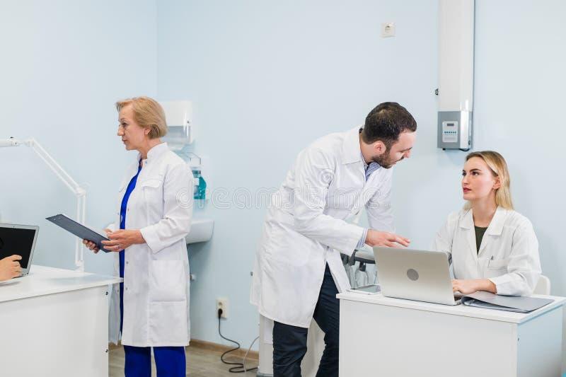 Gruppo di medici allegro in ufficio dentario discutere circa pratica e la lista d'esame dei pazienti fotografie stock