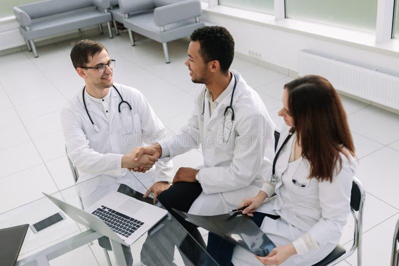 Gruppo di medici che discutono l'anamnesi del paziente ad una riunione di lavoro immagine stock libera da diritti
