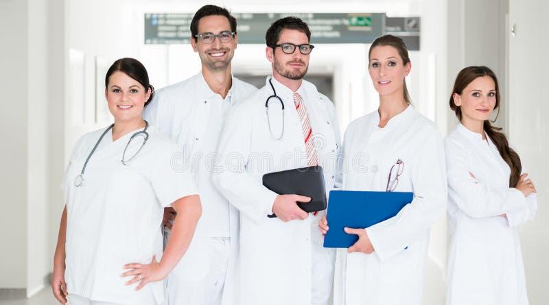 Gruppo di medici che stanno in corridoio dell'ospedale immagine stock libera da diritti