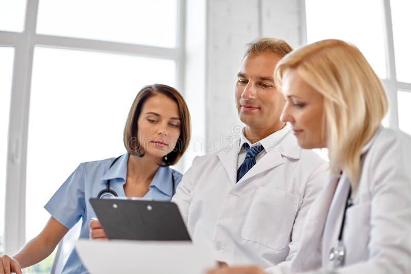 Gruppo di medici con la lavagna per appunti all'ospedale immagini stock libere da diritti