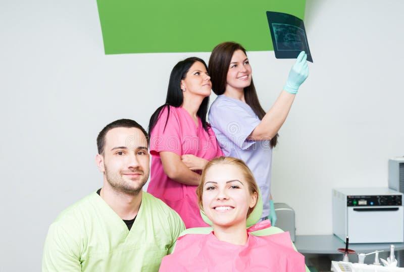 Gruppo di medici dentario con il paziente ed i raggi x fotografie stock