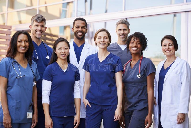 Gruppo di medici sorridente che sta insieme fuori di un ospedale immagini stock