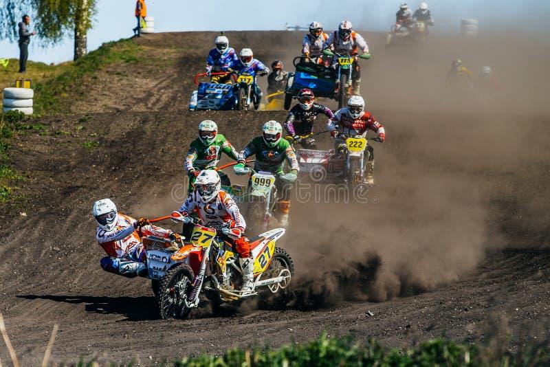Gruppo di motociclisti con i sidecar che guidano lungo una pista polverosa fotografia stock libera da diritti