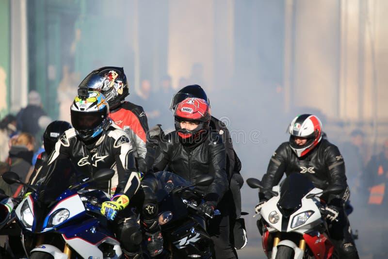 Gruppo di motociclisti in uno schermo di fumo un giorno soleggiato fotografia stock libera da diritti