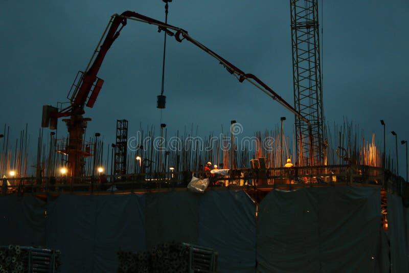 Gruppo di muratori che stanno lavorando ad una costruzione durante la notte con una gru nei precedenti fotografie stock