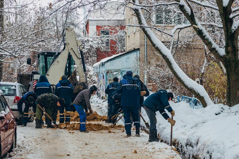 Gruppo di muratori irriconoscibili che riparano i cavi o la conduttura sotterranei di comunicazione fotografie stock