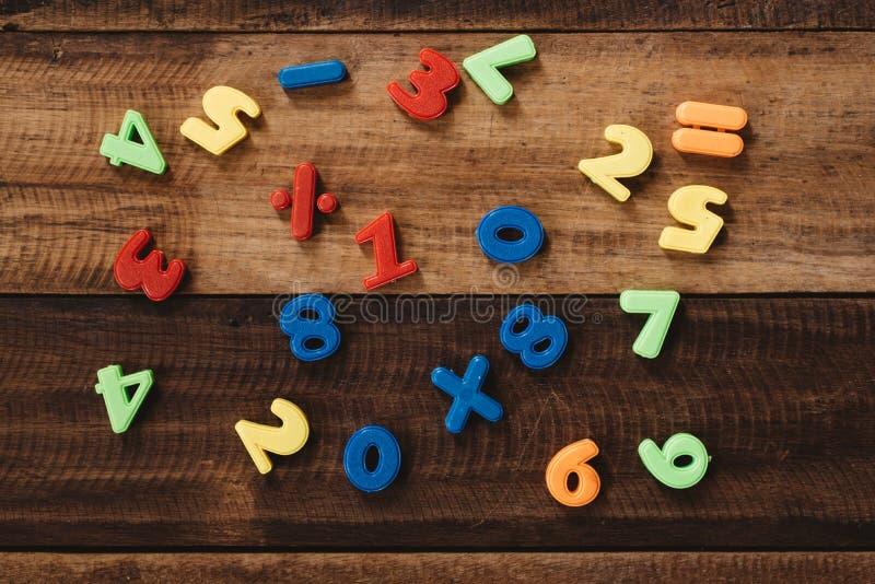 Gruppo di numeri variopinti e di notazione matematica sulla tavola di legno immagini stock libere da diritti