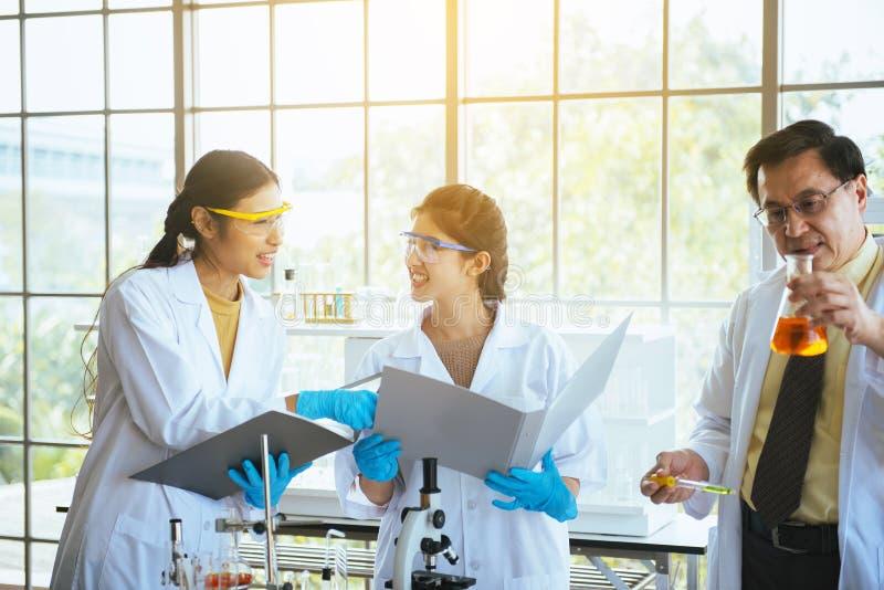 Gruppo di nuovo progetto di giovane della donna ricerca asiatica del chimico con professore dell'uomo al laboratorio fotografia stock libera da diritti