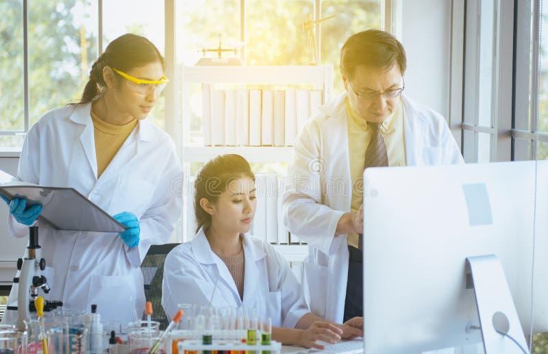 Gruppo di nuovo progetto di ricerca asiatica dello studente di medicina con professore senior insieme al laboratorio fotografie stock libere da diritti