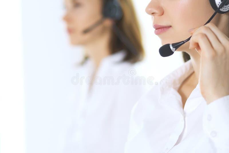 Gruppo di operatori di call center sul lavoro Fuoco alla bella donna di affari in cuffia avricolare fotografia stock