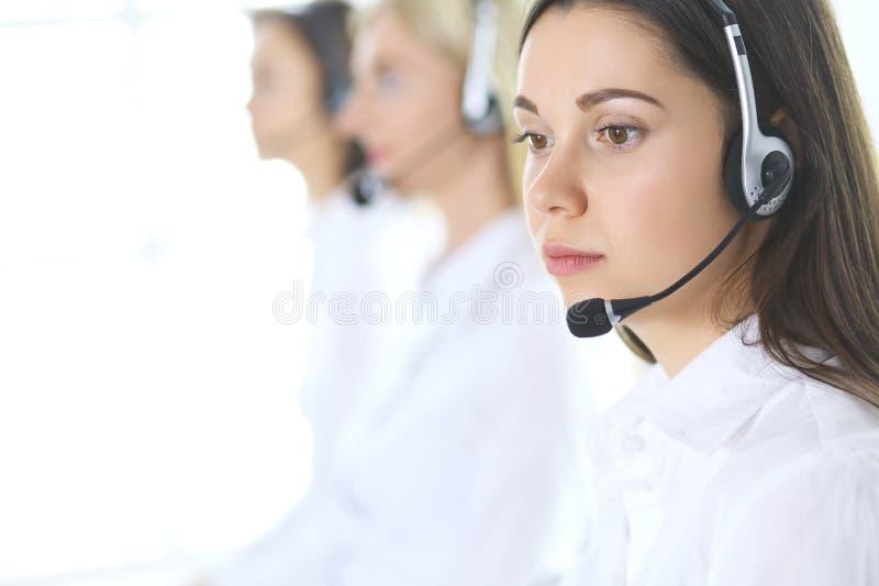 Gruppo di operatori di call center sul lavoro Fuoco alla bella donna di affari in cuffia avricolare fotografie stock