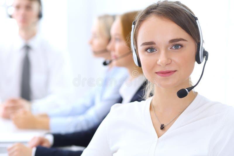 Gruppo di operatori di call center sul lavoro Metta a fuoco alla bella donna bionda di affari in cuffia avricolare fotografia stock