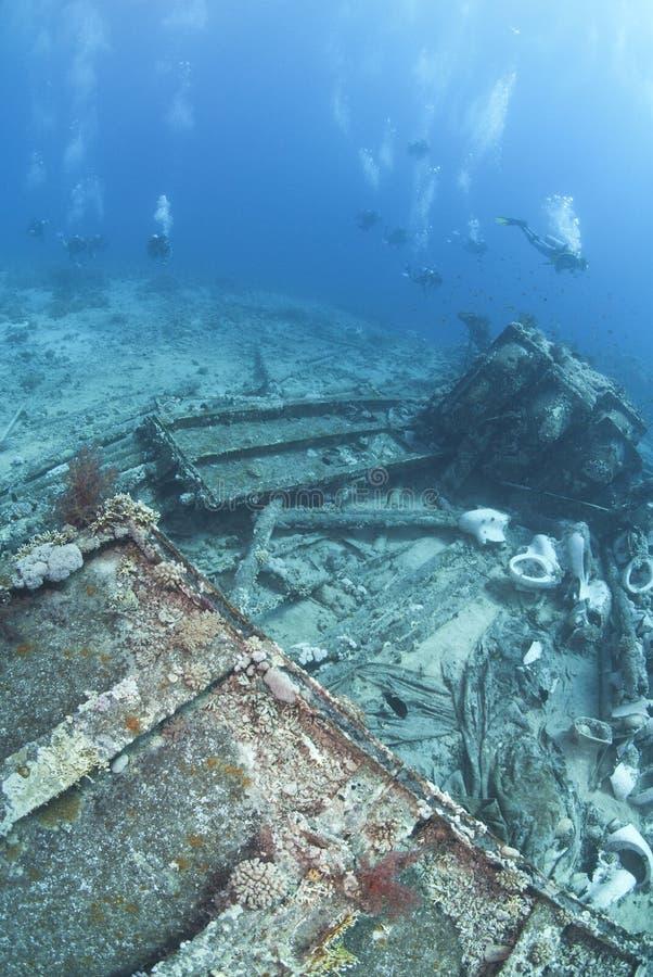 Gruppo di operatori subacquei di scuba che esplorano un naufragio. fotografia stock