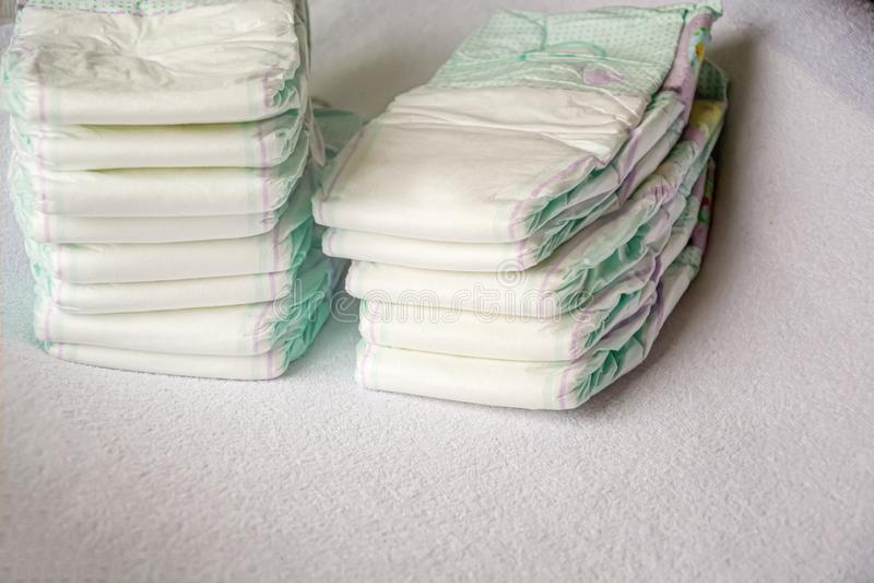 Gruppo di pannolini eliminabili sistemati sopra una tavola cambiante bianca immagine stock libera da diritti