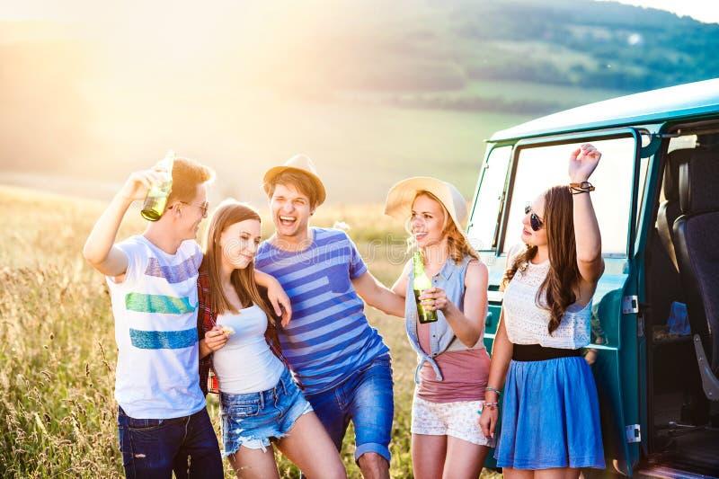 Gruppo di pantaloni a vita bassa adolescenti su un roadtrip, birra bevente fotografia stock libera da diritti