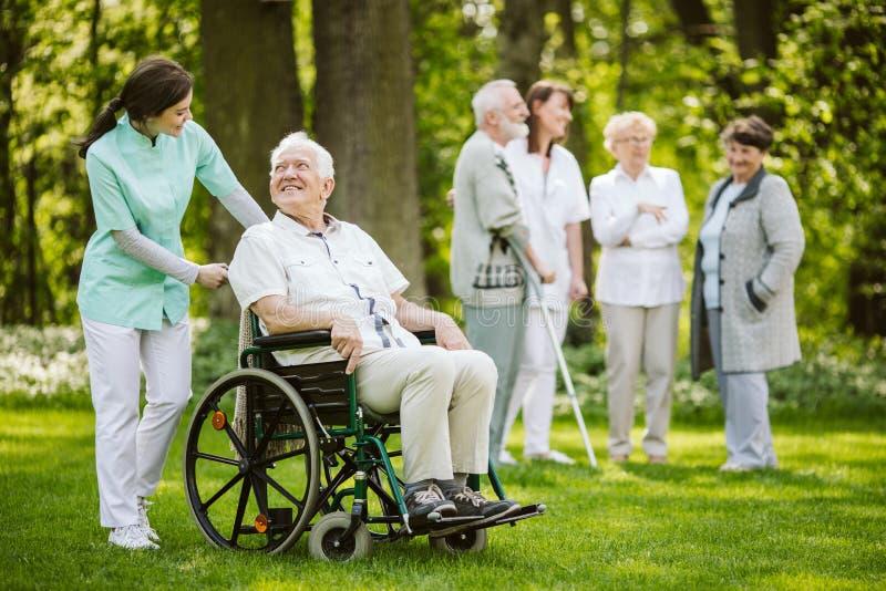 Gruppo di pazienti e di infermieri nella casa di cura immagine stock