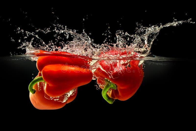Gruppo di peperone dolce che cade in acqua con spruzzata su fondo nero fotografia stock libera da diritti