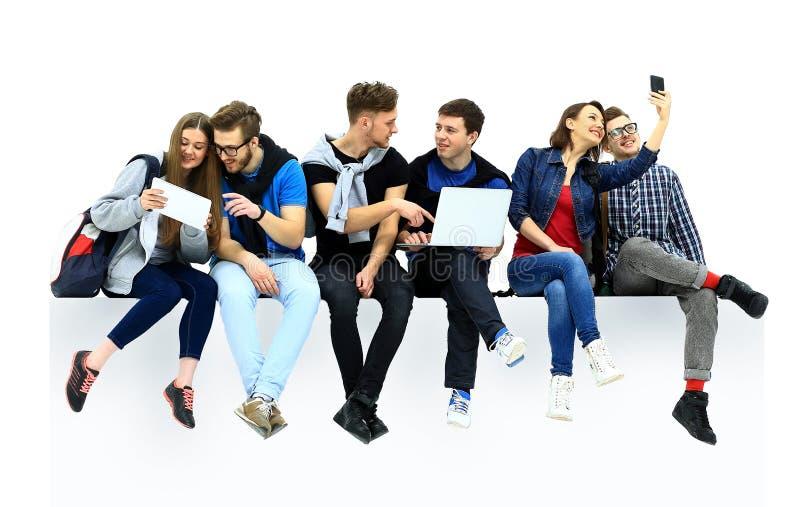 Gruppo di persone causale che si siedono sul pavimento immagini stock