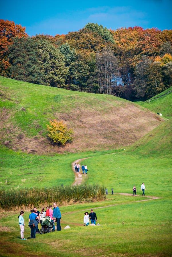 Gruppo di persone che camminano vicino alle colline di Kernave immagine stock