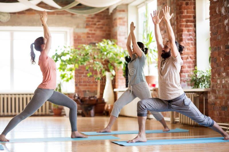 Gruppo di persone che fanno posa del guerriero di yoga allo studio fotografia stock libera da diritti