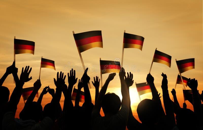 Gruppo di persone che ondeggiano le bandiere tedesche in Lit posteriore immagine stock libera da diritti