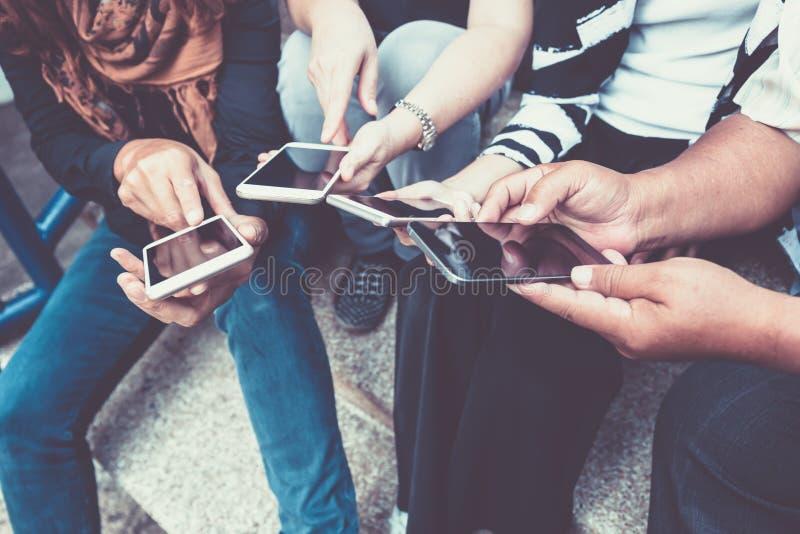 Gruppo di persone che per mezzo dello Smart Phone fotografia stock