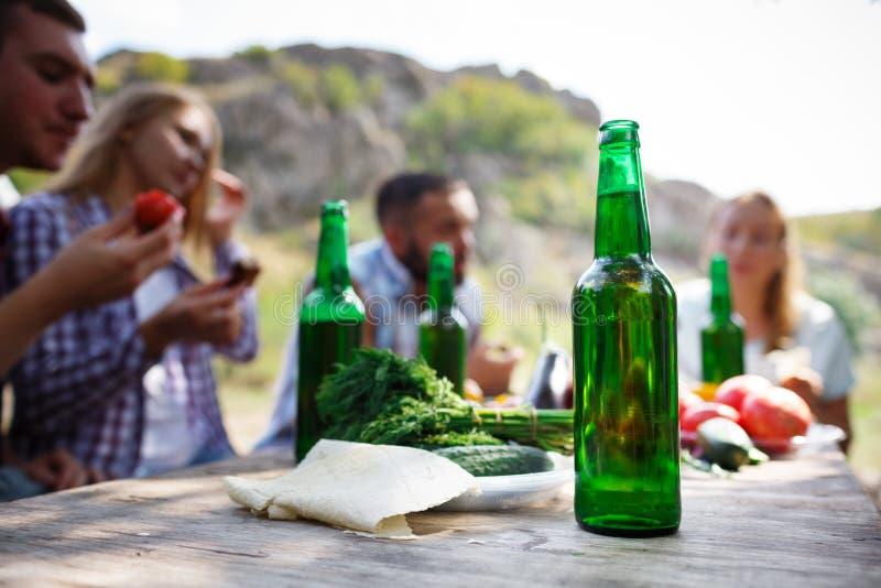 Gruppo di persone che pranzano concetto di unità I migliori amici stanno bevendo la birra saporita su un picnic dell'estate fotografia stock