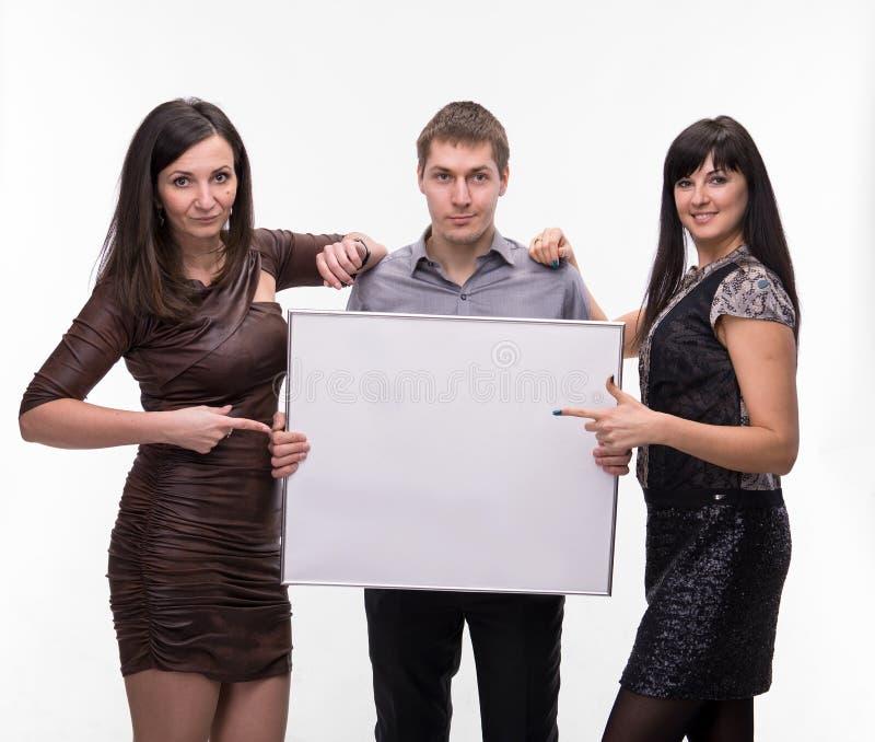 Gruppo di persone che presentano insegna in bianco fotografia stock