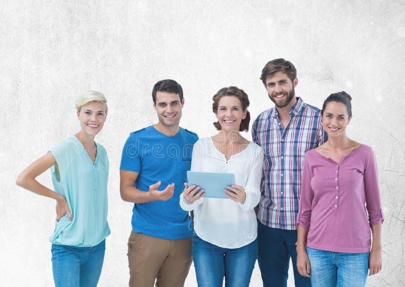 Gruppo di persone che stanno davanti al fondo grigio in bianco fotografia stock libera da diritti