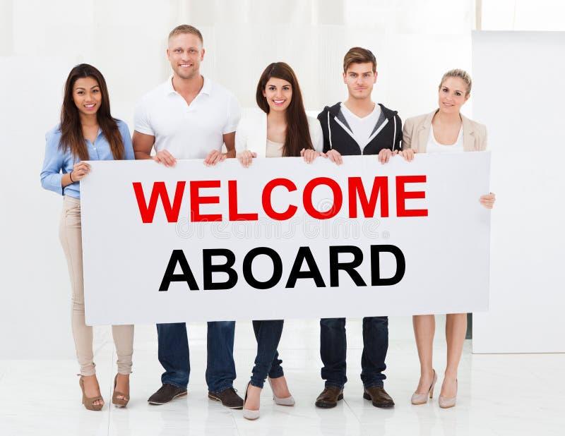 Gruppo di persone che tengono benvenuto a bordo del cartello fotografia stock