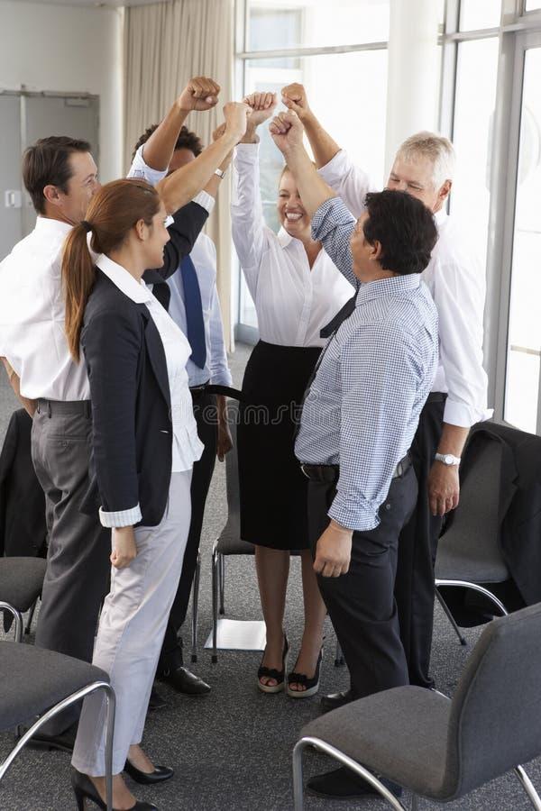Gruppo di persone di affari con le armi alzate al seminario della società fotografia stock libera da diritti