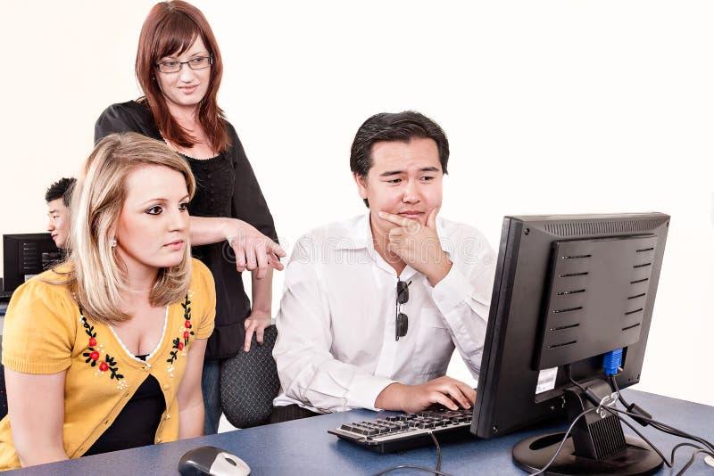 Gruppo di persone gli sguardi al monitor del computer fotografia stock