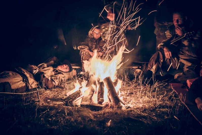 Gruppo di persone i turisti che si rilassano dal fuoco nel campo di aria aperta dopo il giorno lungo di caccia nella notte fotografia stock