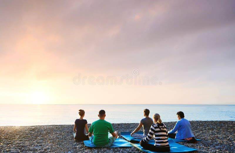 Gruppo di persone la meditazione di pratica di mattina, aria aperta di yoga ad alba sulla spiaggia Ritenere cos? comodo e rilassa fotografie stock