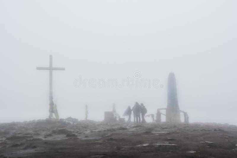 Gruppo di persone vicino all'incrocio ed il monumento nella nebbia fotografia stock libera da diritti