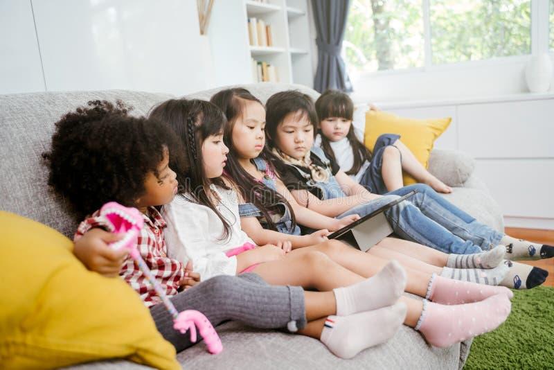 Gruppo di piccoli bambini che guardano insieme il fumetto di film del film sulla compressa digitale Bambini che giocano con la co fotografie stock libere da diritti